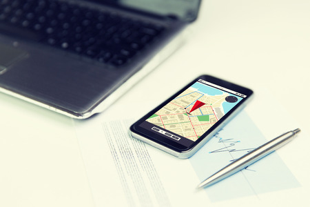 gprs: business, technology, navigation and location concept - close up of smartphone with gps navigator map on screen, laptop computer and pen on office table
