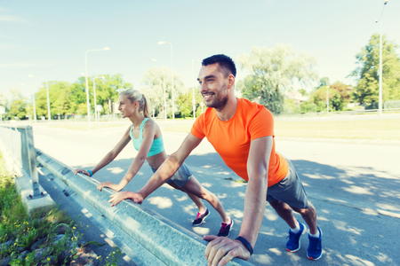 pareja saludable: fitness, sport, training and healthy lifestyle concept - close up of happy couple doing push-ups outdoors