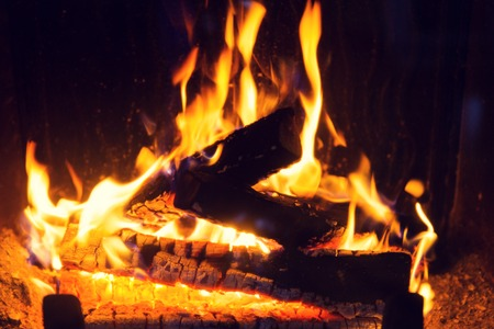 hotbed: heating, warmth, fire and cosiness concept - close up of firewood burning in fireplace Stock Photo