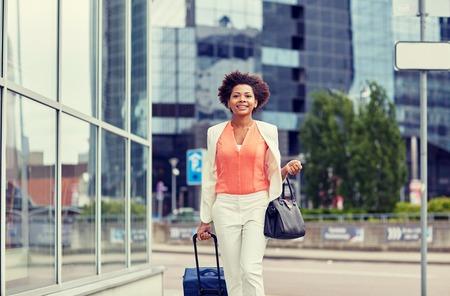 viajes, viaje de negocios, la gente y el concepto de turismo - African American mujer joven feliz con bolsa de viaje caminando por calle de la ciudad