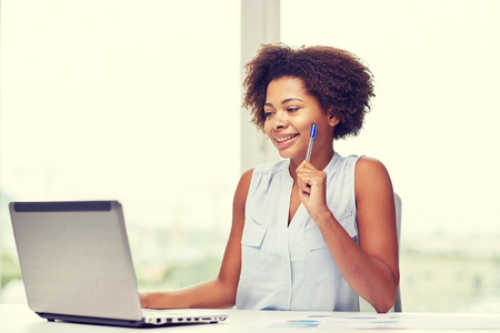 learning online: education, business and technology concept - happy african american businesswoman or student with laptop computer and papers at office