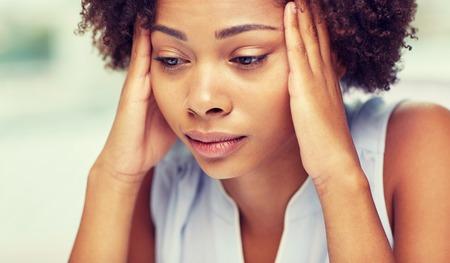 las personas, las emociones, el estrés y el concepto del cuidado de la salud - infeliz mujer joven afroamericano que toca su cabeza y que sufren de dolor de cabeza