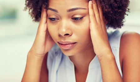 suffering: people, emotions, stress and health care concept - unhappy african american young woman touching her head and suffering from headache