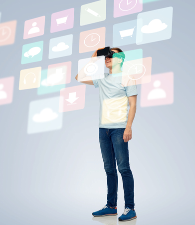 modified: 3d technology, virtual reality, entertainment, cyberspace and people concept - happy young man with virtual reality headset or 3d glasses looking at screen with menu icons Stock Photo