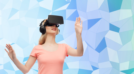 entertainment background: technology, virtual reality, entertainment and people concept - happy young woman with virtual reality headset or 3d glasses and headphones playing game over blue low poly texture background Stock Photo