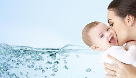 wasser: Familie, Mutterschaft, Menschen und Kinderbetreuung Konzept - glückliche Mutter adorable Baby auf blauem Hintergrund mit Wasser spritzen küssen