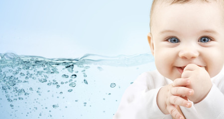 babyhood: people, babyhood, child care and advertisement concept - close up of happy baby boy over blue background with water splash