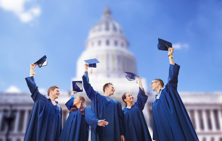 education, graduation and people concept - group of happy smiling students in gowns waving mortarboards over washington white house background Stock Photo