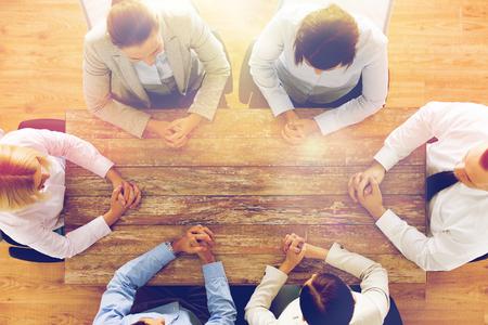 entreprise, les gens et le concept de travail d'équipe - rapproché de l'équipe créative assis à une table dans le bureau