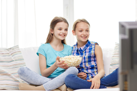 two children: people, children, television, friends and friendship concept - two happy little girls with popcorn watching tv at home