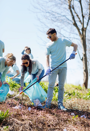 medio ambiente: el voluntariado, la caridad, la limpieza, la gente y el concepto de ecología - grupo de voluntarios felices con bolsas de basura área de limpieza en el parque