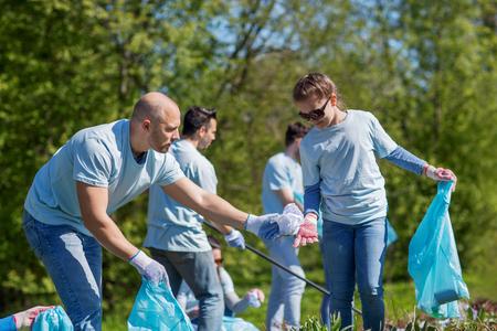 vrijwilligerswerk, liefdadigheid, het schoonmaken, mensen en ecologie concept - groep gelukkige vrijwilligers met vuilniszakken schoonmaken gebied in park