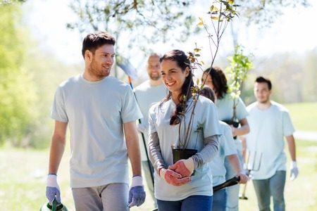 welfare plant: volunteering, charity, people and ecology concept - group of happy volunteers with tree seedlings and rake walking in park