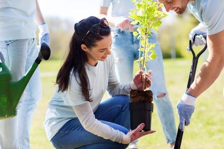 vrijwilligerswerk, liefdadigheid, mensen en ecologie concept - groep gelukkige vrijwilligers het planten van bomen en het graven gat met schop in park Stockfoto