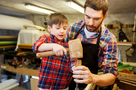 family, carpentry, woodwork and people concept - father and little son with hammer and chisel working with wood plank at workshop Stock Photo