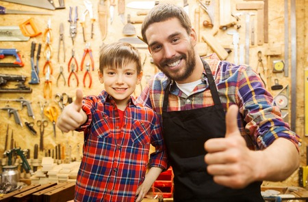 family, carpentry, woodwork, gesture and people concept - happy father and little son making thumbs up at workshop Foto de archivo