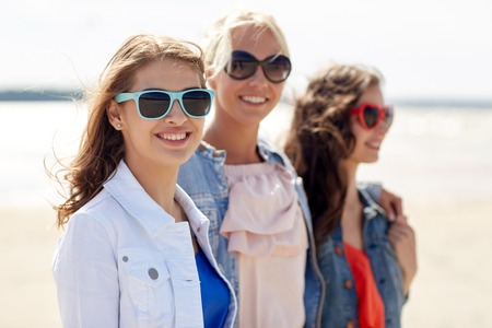 style woman: summer vacation, holidays, travel and people concept - group of smiling young women in sunglasses and casual clothes on beach