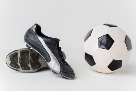 football cleats: sport, soccer, football and sports equipment concept - close up of ball and boots