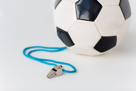 sport object: sport, soccer, football, refereeing and sports equipment concept - close up of ball and referee whistle