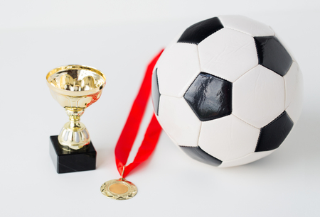 white achievement: sport, achievement, championship, competition and success concept - close up of football or soccer ball with golden medal and cup over white background