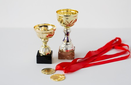 white achievement: sport, achievement, reward, championship and success concept - close up of sports golden cups and medals on white background