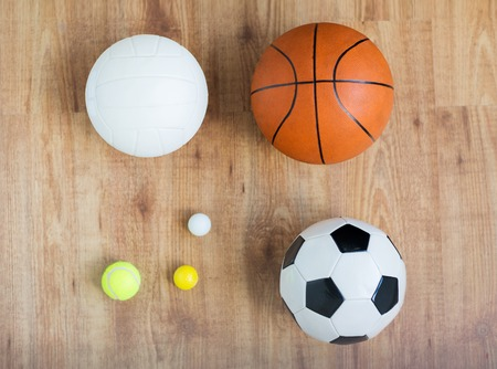 objects equipment: sport, fitness, game, sports equipment and objects concept - close up of different sports balls set on wooden floor from top Stock Photo