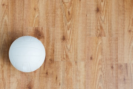 objects equipment: sport, fitness, game, sports equipment and objects concept - close up of volleyball ball on wooden floor from top