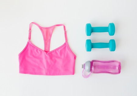 sport, fitness, healthy lifestyle and objects concept - close up of sports top, dumbbells and water bottle over white background