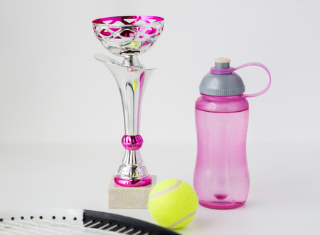 white achievement: sport, achievement, championship, competition and success concept - close up of tennis racket and ball with cup and bottle over white background