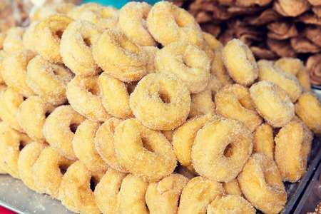 sugarcoated: cooking, asian kitchen, sale and food concept - sugared donuts at asian street market