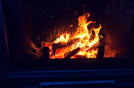 hotbed: heating, warmth, fire and cosiness concept - close up of burning fireplace at home