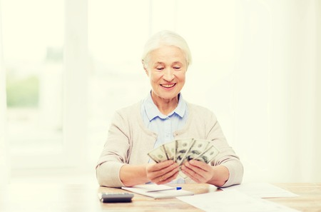 business savings: business, savings, annuity insurance, age and people concept - happy senior woman with calculator and bills counting dollar money at home