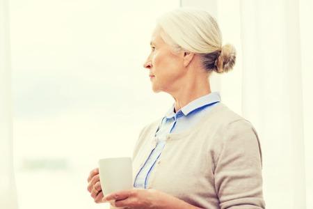 soledad: la edad, la soledad y el concepto de la gente - mujer mayor sola con la taza de té o café mirando por la ventana en el hogar Foto de archivo