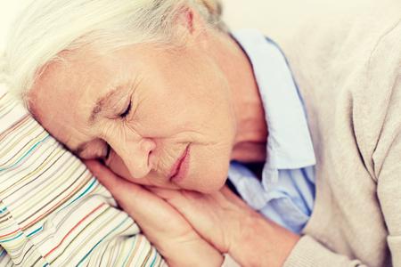gente durmiendo: la edad, la gente se relaje y concepto - mujer mayor feliz duerme en la almohadilla en el hogar Foto de archivo