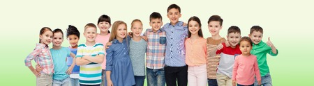 casual clothing: childhood, fashion, friendship and people concept - group of happy smiling children hugging over green natural background Stock Photo