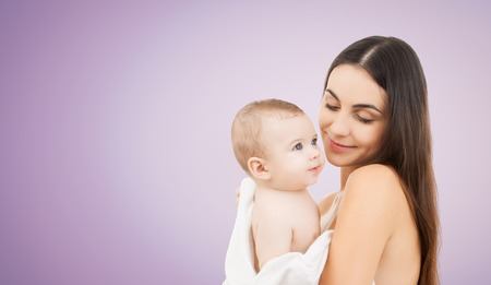 family, motherhood, parenting, people and child care concept - happy mother holding adorable baby over violet background