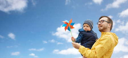 family, childhood, fatherhood, leisure and people concept - happy father and little son with pinwheel toy over blue sky and clouds background Banco de Imagens