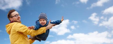 familie, jeugd, vaderschap, vrije tijd en mensen concept - gelukkige vader en zoontje spelen en plezier over blauwe hemel en de wolken achtergrond