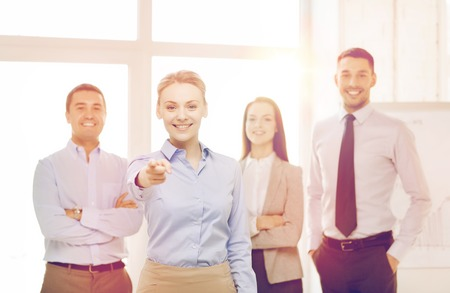 work group: business and office concept - smiling handsome businesswoman with team in office pointing finger at you