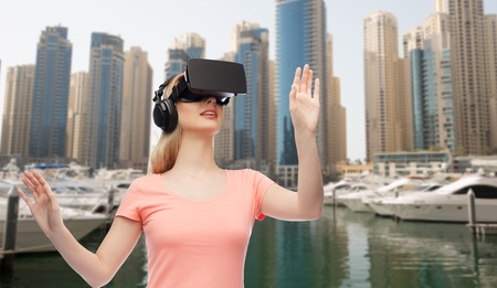 entertainment background: technology, virtual reality, entertainment, travel and people concept - happy young woman with virtual reality headset or 3d glasses and headphones playing game over dubai city street background