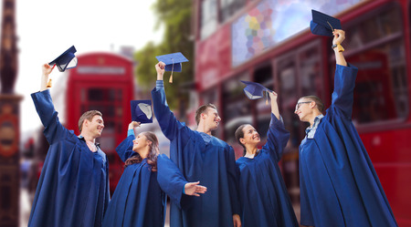 kingdom: education, graduation and people concept - group of happy smiling students in gowns waving mortarboards over london city street background