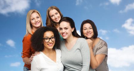 grupos de personas: la amistad, la moda, el cuerpo positivo, diversa y concepto de las personas - grupo de mujeres felices en ropa casual diferentes sobre el cielo azul y las nubes de fondo Foto de archivo