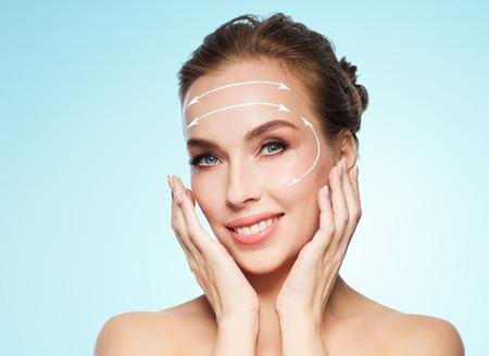 la beauté, la chirurgie plastique, lifting, les gens et le concept de rajeunissement - belle jeune femme de toucher son visage avec des flèches de levage sur fond bleu Banque d'images