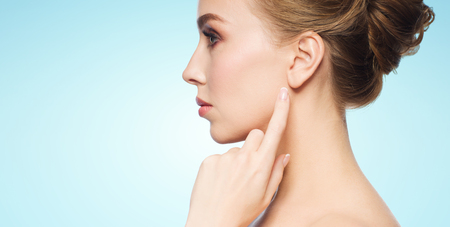 health, people and beauty concept - beautiful young woman pointing finger to her ear over blue background Stock Photo