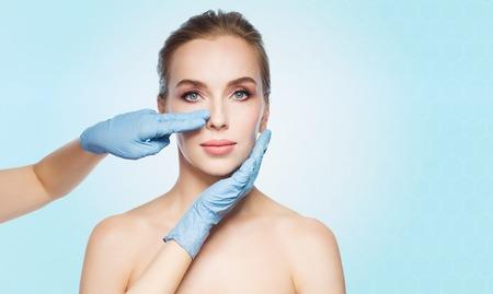 Les gens, la cosmétologie, la chirurgie et la beauté plastique concept - chirurgien ou mains esthéticienne touchante visage de femme sur fond bleu Banque d'images - 63325205
