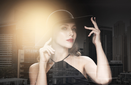 people, luxury and fashion concept - beautiful woman in black hat over dark over dubai city background with double exposure and highlight