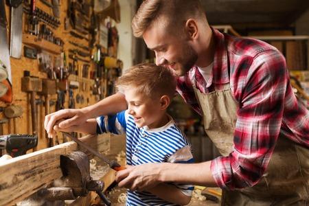 家族、大工、木工事および人々 のコンセプト - 幸せな父と幼い息子のワーク ショップで木の板を研磨やすりで