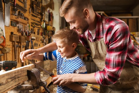 La familia, la carpintería, la carpintería y la gente concepto - padre feliz y el pequeño hijo con la escofina de molienda de tablones de madera en el taller Foto de archivo - 63311421