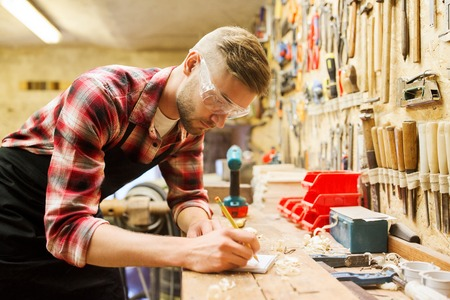 profession, carpentry, woodwork and people concept - carpenter with pencil writing to notebook at workshop Stock Photo