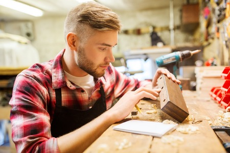chippy: profession, carpentry, woodwork and people concept - carpenter working with wood plank at workshop